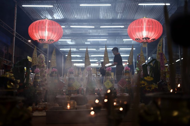 A young Ethnic Chinese devotee offers prayers during Chinese Hungry Ghost Festival inside Kuala Lumpur on August 04, 2014. In the Chinese tradition the seventh month of the lunar year is regarded as the Ghost Month in which spirits and ghosts come down to earth. The devotees also will do a ritualistic food offerings, burning incense, burning joss paper and burning a paper-made models such as clothes, gold, sport cars and other fine goods to appease wandering spirits. Photo Adib Rawi Yahya
