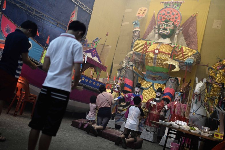 An Ethnic Chinese devotee offers prayers in front of paper-made statue during Chinese Hungry Ghost Festival inside Kuala Lumpur on August 04, 2014. In the Chinese tradition the seventh month of the lunar year is regarded as the Ghost Month in which spirits and ghosts come down to earth. The devotees also will do a ritualistic food offerings, burning incense, burning joss paper and burning a paper-made models such as clothes, gold, sport cars and other fine goods to appease wandering spirits. Photo Adib Rawi Yahya