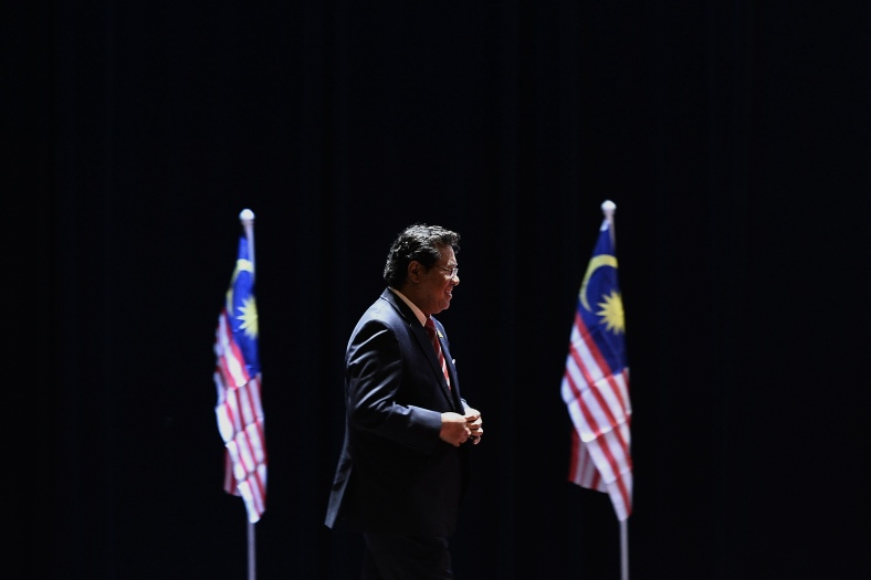 Selangor mentri besar Khalid Ibrahim walks pass the Jalur Gemilang at a function at Shah Alam outside Kuala Lumpur on August 25, 2014. Khalid Ibrahim will meet with the Selangor Sultan some time where he is expected to discuss his tenuous position as the state's mentri besar and Pakatan Rakyat (PR) leaders urged their former colleague to step down gracefully as mentri besar and spare Selangor the costly outcome of statewide polls. Photo Adib Rawi Yahya