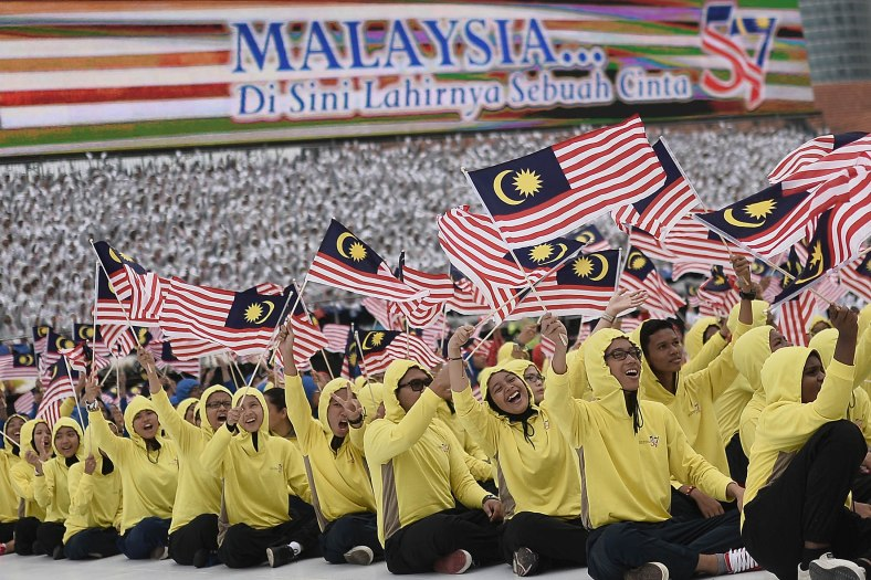 Students joyfully wave flags during a rehearsal for the 57th Merdeka celebrations at Dataran Merdeka in Kuala Lumpur on August 29, 2014. 'Malaysia...Di Sini Lahirnya Sebuah Cinta' is the official theme of this year's Merdeka. The theme is taken from the lyrics of the song 'Warisan' popularised by the late Sudirman Haji Arshad. Photo Adib Rawi Yahya