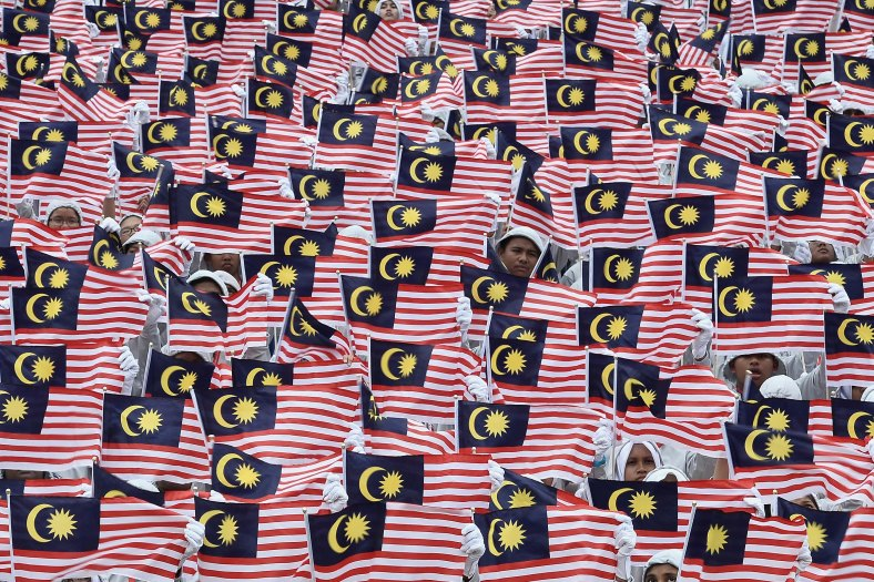 Students hold Jalur Gemilang during a rehearsal for the 57th Merdeka celebrations at Dataran Merdeka in Kuala Lumpur on August 29, 2014. 'Malaysia...Di Sini Lahirnya Sebuah Cinta' is the official theme of this year's Merdeka. The theme is taken from the lyrics of the song 'Warisan' popularised by the late Sudirman Haji Arshad. Photo Adib Rawi Yahya