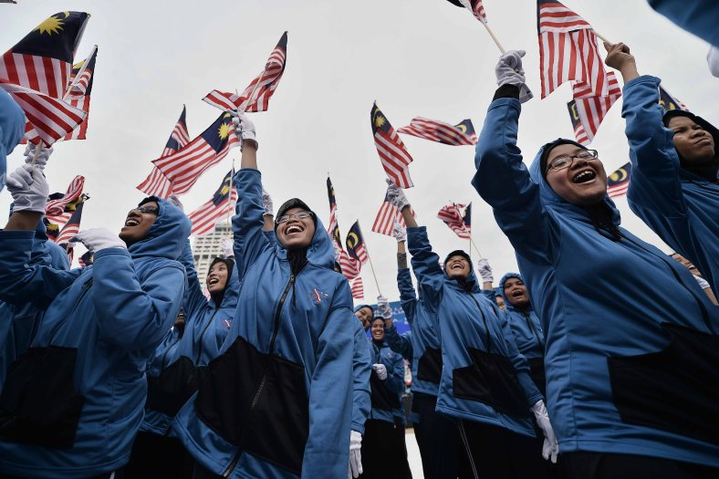 Students joyfully wave flags and sing patriotic songs during a rehearsal for the 57th Merdeka celebrations at Dataran Merdeka in Kuala Lumpur on August 29, 2014. 'Malaysia...Di Sini Lahirnya Sebuah Cinta' is the official theme of this year's Merdeka. The theme is taken from the lyrics of the song 'Warisan' popularised by the late Sudirman Haji Arshad. Photo Adib Rawi Yahya
