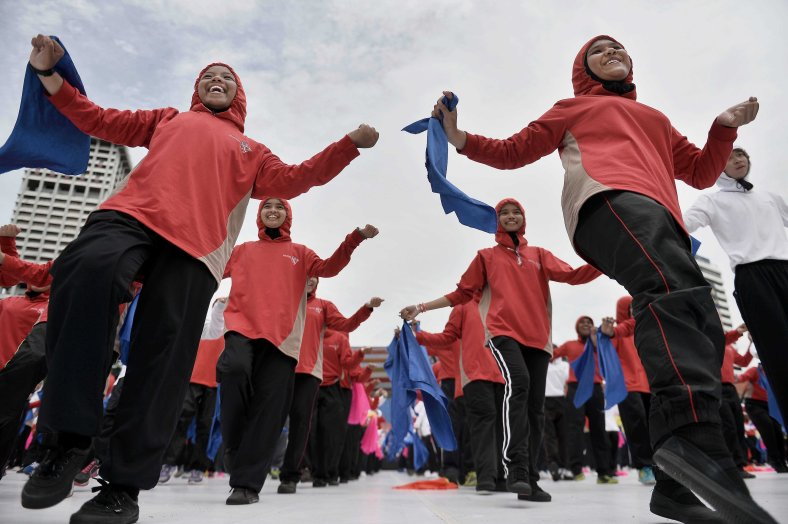 Students joyfully and sing patriotic songs during a rehearsal for the 57th Merdeka celebrations at Dataran Merdeka in Kuala Lumpur on August 29, 2014. 'Malaysia...Di Sini Lahirnya Sebuah Cinta' is the official theme of this year's Merdeka. The theme is taken from the lyrics of the song 'Warisan' popularised by the late Sudirman Haji Arshad. Photo Adib Rawi Yahya