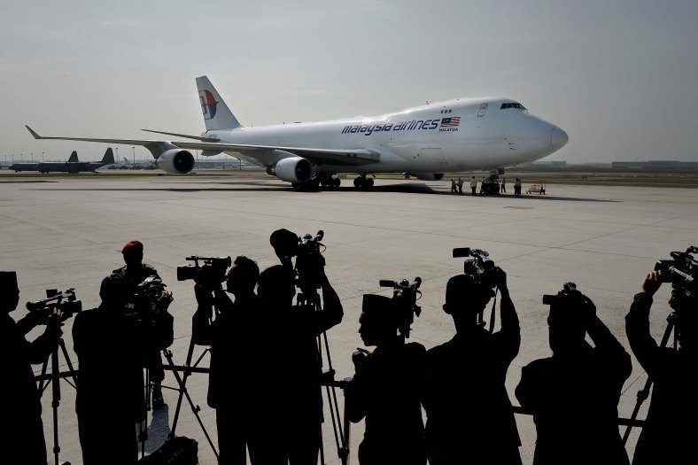 Members of the media get a shot of the aircraft that carried the remains of the MH17 flight victims during of the ceremony honouring on August 22, 2014. A plane bring back home the first remains of the 43 Malaysians on the ill-fated Malaysia Airlines plane that was shot down in east of Ukraine on July 17 during a flight from Amsterdam to Kuala Lumpur. In total 298 people lost their lives in the tragedy. Photo Adib Rawi Yahya