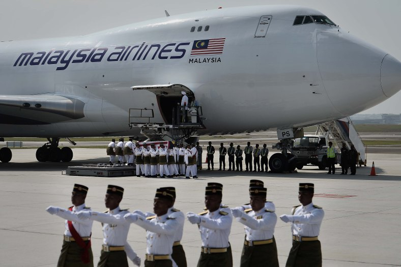 Malaysia Army personnel carry the coffin with the remains of a Malaysian victim from the Malaysia Airlines flight MH17 that crashed in Ukraine during of the ceremony honouring at KL International Airport (KLIA) on August 22, 2014. A plane bring back home the first remains of the 43 Malaysians on the ill-fated Malaysia Airlines plane that was shot down in east of Ukraine on July 17 during a flight from Amsterdam to Kuala Lumpur. In total 298 people lost their lives in the tragedy. Photo Adib Rawi Yahya