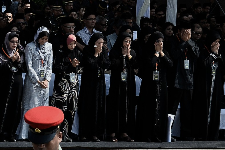 Family members and next-of-kin of the Malaysia Airlines flight MH17 victims pause for a moment of silence during of the ceremony honouring at KL International Airport (KLIA) on August 22, 2014. A plane bring back home the first remains of the 43 Malaysians on the ill-fated Malaysia Airlines plane that was shot down in east of Ukraine on July 17 during a flight from Amsterdam to Kuala Lumpur. In total 298 people lost their lives in the tragedy. Photo Adib Rawi Yahya