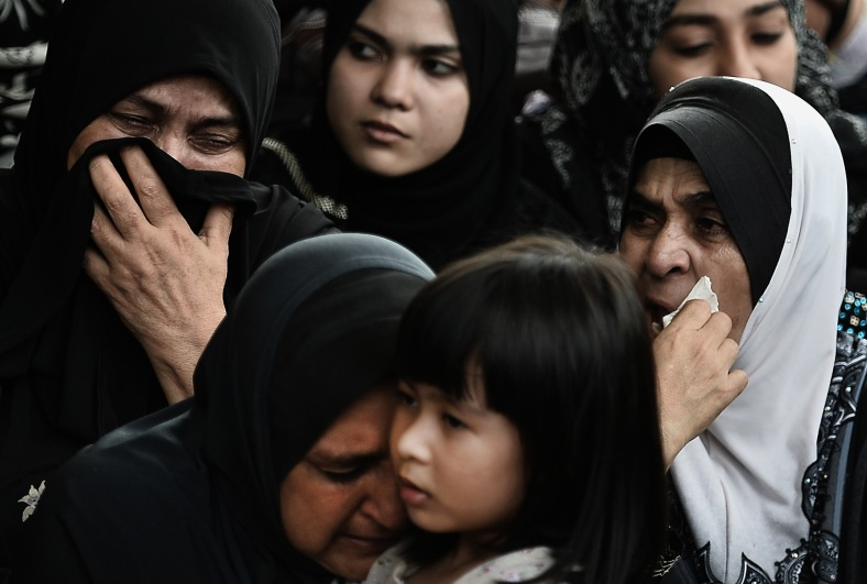 Family members of late co-pilot Ahmad Hakimi Hanapi, who perished aboard flight MH17 downed in eastern Ukraine, attends a burial ceremony in Putrajaya, outside Kuala Lumpur on August 22, 2014. A plane bring back home the first remains of the 43 Malaysians on the ill-fated Malaysia Airlines plane that was shot down in east of Ukraine on July 17 during a flight from Amsterdam to Kuala Lumpur. In total 298 people lost their lives in the tragedy. Photo Adib Rawi Yahya
