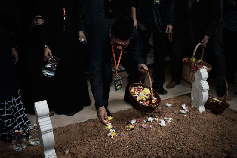 The father of Malaysia Airlines flight attendant Nur Shazana, one of the Malaysians who perished aboard flight MH17 downed in eastern Ukraine, puts flowers on his daughter's grave during a burial ceremony in Putrajaya, outside Kuala Lumpur on August 22, 2014. A plane bring back home the first remains of the 43 Malaysians on the ill-fated Malaysia Airlines plane that was shot down in east of Ukraine on July 17 during a flight from Amsterdam to Kuala Lumpur. In total 298 people lost their lives in the tragedy. Photo Adib Rawi Yahya