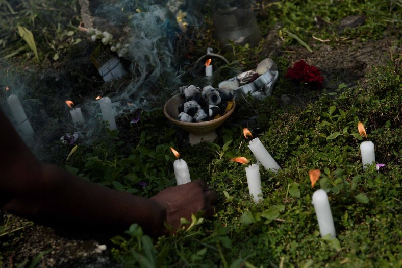 """Relatives light candles, offer flowers and say prayers at the tomb stone of their departed love ones during All Souls Day festival at a cemetery outside Kuala Lumpur on November 2, 2014. All Souls Day is a day of prayer for the dead, particularly but not exclusively one's relatives which is observed on Nov 2 every year, also goes by its official name as """"The Commemoration of All the Faithful Departed"""". Photo Adib Rawi Yahya"""