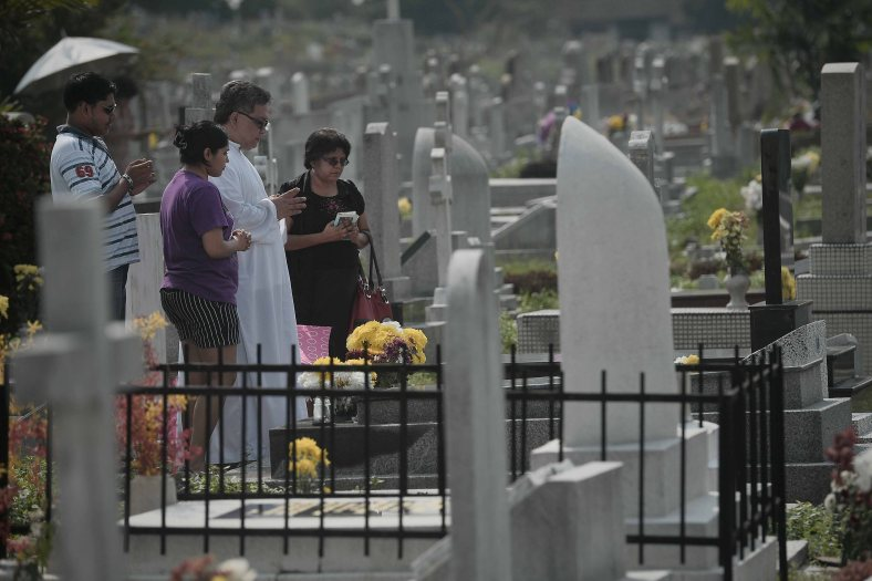 """Relatives together with father offer flowers and say prayers at the tomb stone of their departed love ones during All Souls Day festival at a cemetery outside Kuala Lumpur on November 2, 2014. All Souls Day is a day of prayer for the dead, particularly but not exclusively one's relatives which is observed on Nov 2 every year, also goes by its official name as """"The Commemoration of All the Faithful Departed"""". Photo Adib Rawi Yahya"""