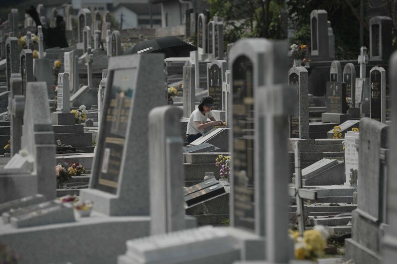 """A relatives clean up the tomb stone of their departed love ones during All Souls Day festival at a cemetery outside Kuala Lumpur on November 2, 2014. All Souls Day is a day of prayer for the dead, particularly but not exclusively one's relatives which is observed on Nov 2 every year, also goes by its official name as """"The Commemoration of All the Faithful Departed"""". Photo Adib Rawi Yahya"""