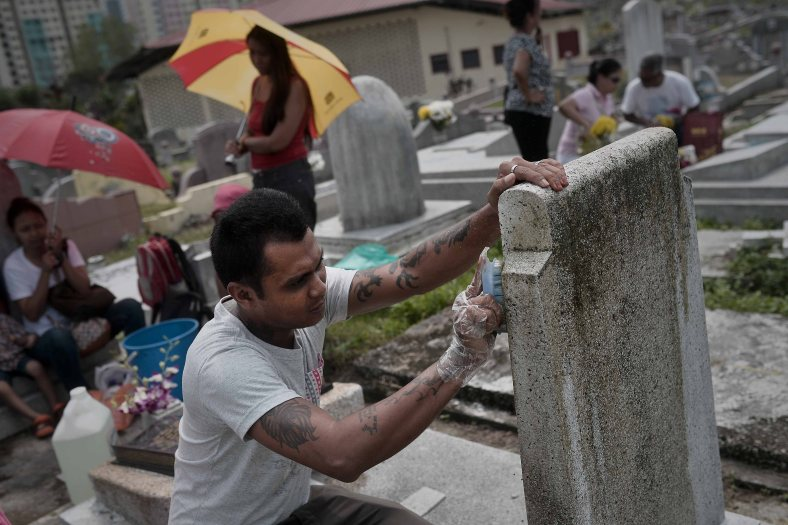 """A man clean up the tomb stone of their departed love ones during All Souls Day festival at a cemetery outside Kuala Lumpur on November 2, 2014. All Souls Day is a day of prayer for the dead, particularly but not exclusively one's relatives which is observed on Nov 2 every year, also goes by its official name as """"The Commemoration of All the Faithful Departed"""". Photo Adib Rawi Yahya"""