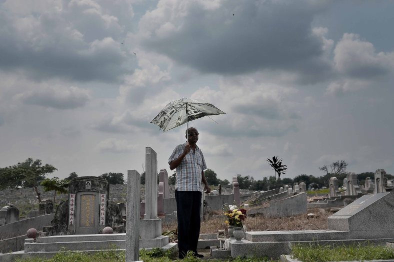 """A relatives stand near the tomb stone of their departed love ones during All Souls Day festival at a cemetery outside Kuala Lumpur on November 2, 2014. All Souls Day is a day of prayer for the dead, particularly but not exclusively one's relatives which is observed on Nov 2 every year, also goes by its official name as """"The Commemoration of All the Faithful Departed"""". Photo Adib Rawi Yahya"""