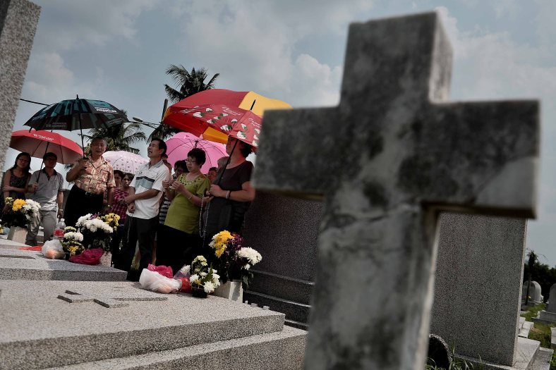 """Relatives offer flowers and say prayers at the tomb stone of their departed love ones during All Souls Day festival at a cemetery outside Kuala Lumpur on November 2, 2014. All Souls Day is a day of prayer for the dead, particularly but not exclusively one's relatives which is observed on Nov 2 every year, also goes by its official name as """"The Commemoration of All the Faithful Departed"""". Photo Adib Rawi Yahya"""