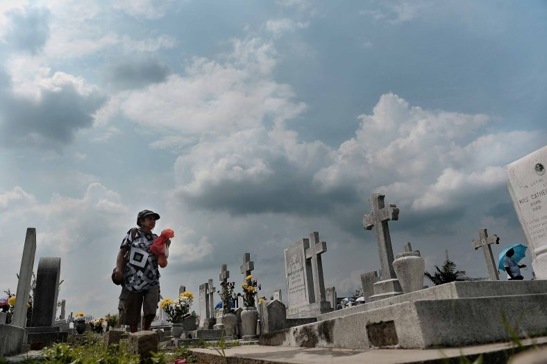 """A woman offer flowers at the tomb stone of their departed love ones during All Souls Day festival at a cemetery outside Kuala Lumpur on November 2, 2014. All Souls Day is a day of prayer for the dead, particularly but not exclusively one's relatives which is observed on Nov 2 every year, also goes by its official name as """"The Commemoration of All the Faithful Departed"""". Photo Adib Rawi Yahya"""