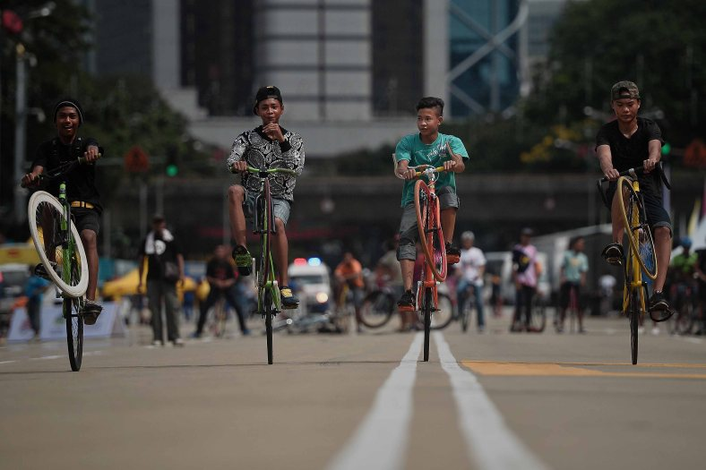 "Fixie Family Malaysia perform 'wheelie' in front of the Sultan Abdul Samad Building during ""KL Car Free Morning"" at Dataran Merdeka on November 02, 2014. Kuala Lumpur City Hall will increasing the frequency of ""KL Car Free Morning"" to twice a month. The monthly event was mooted by Kuala Lumpur mayor Datuk Seri Ahmad Phesal Talib and introduced in January to promote a greener city and reduce global warming. Photo Adib Rawi Yahya"
