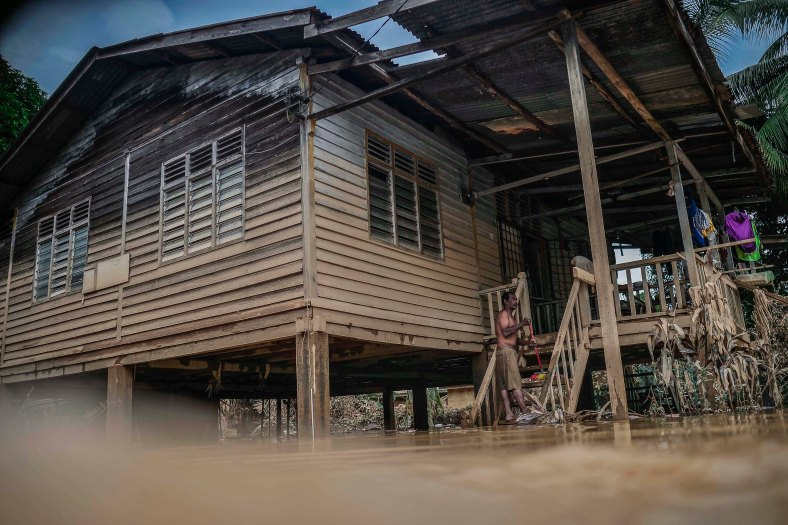 A resident cleans out his house that was flooded in heavy rains at Temerloh, Pahang on January 04, 2015. In Pahang, 29,547 evacuees were recorded in 126 centres in seven affected areas. Temerloh has the 2nd largest number of victims with 10,576 people after Pekan. photo Adib Rawi Yahya
