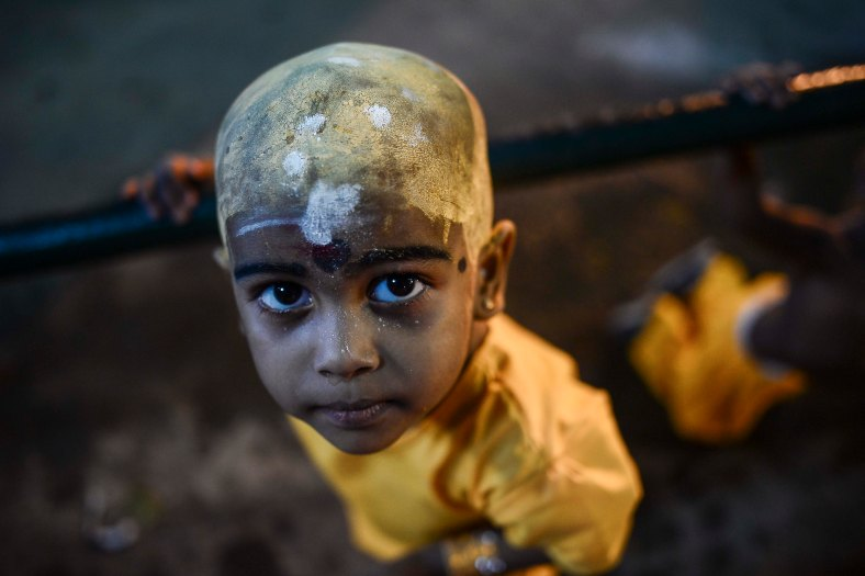 A young Malaysian Hindu devotees makes his way towards the temple to perform religious rites during the Thaipusam festival at Batu Caves outskirts of Kuala Lumpur on February 03, 2015. The Hindu festival of Thaipusam, which commemorates the day when Goddess Pavarthi gave her son Lord Muruga an invincible lance with which he destroyed evil demons, is celebrated by some two million ethnic Indians in Malaysia and Singapore. photo Adib Rawi Yahya