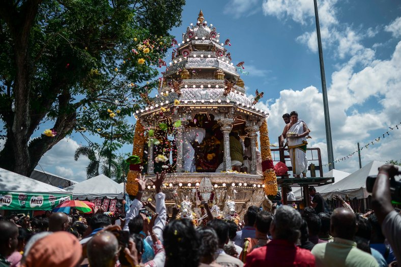 Malaysian Hindu devotees present their offerings to Lord Muruga whose statue is taken in a silver chariot during the Thaipusam festival at Batu Caves outskirts of Kuala Lumpur on February 03, 2015. The Hindu festival of Thaipusam, which commemorates the day when Goddess Pavarthi gave her son Lord Muruga an invincible lance with which he destroyed evil demons, is celebrated by some two million ethnic Indians in Malaysia and Singapore. photo Adib Rawi Yahya
