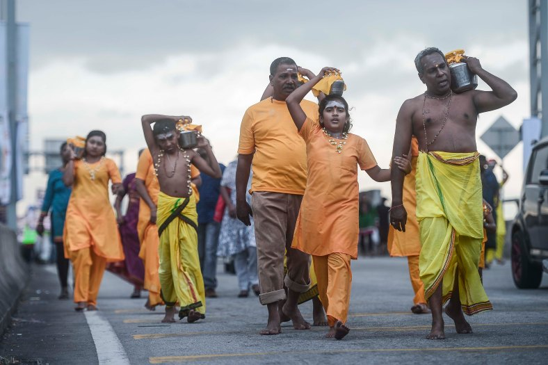 Malaysian Hindu devotees carry milk pots on their heads intended as perform their religious rites during the Thaipusam festival at Batu Caves outskirts of Kuala Lumpur on February 03, 2015. The Hindu festival of Thaipusam, which commemorates the day when Goddess Pavarthi gave her son Lord Muruga an invincible lance with which he destroyed evil demons, is celebrated by some two million ethnic Indians in Malaysia and Singapore. photo Adib Rawi Yahya