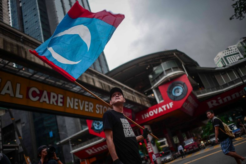 A supporter of Malaysia's opposition leader Anwar Ibrahim holds Keadilan flag during 'KitaLawan' (We Fight) rally in Kuala Lumpur on March 28, 2015. #KitaLawan rally today will call for opposition leader Datuk Seri Anwar Ibrahim's release from jail where he is serving time for sodomy, and for Prime Minister Datuk Seri Najib Razak's resignation. The demonstration has added opposition to the 6% goods and services tax (GST) to today's agenda and also coincides with the wedding reception of Najib's daughter, Nooryana Najwa, held at the Kuala Lumpur Convention Centre on the same day. photo Adib Rawi Yahya