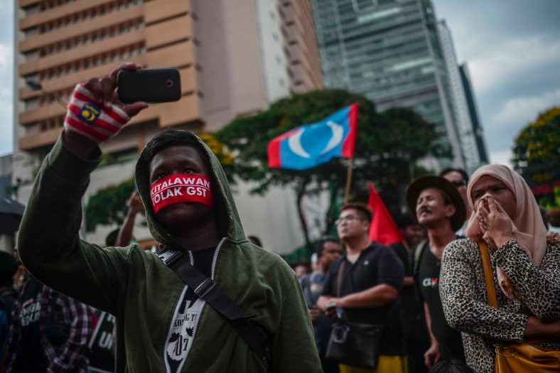 A supporter of Malaysia's opposition leader Anwar Ibrahim take a photo while wears a headband 'KitaLawan Tolak GST' that translates to 'we will fight No GST' during 'KitaLawan' (We Fight) rally in Kuala Lumpur on March 28, 2015. #KitaLawan rally today will call for opposition leader Datuk Seri Anwar Ibrahim's release from jail where he is serving time for sodomy, and for Prime Minister Datuk Seri Najib Razak's resignation. The demonstration has added opposition to the 6% goods and services tax (GST) to today's agenda and also coincides with the wedding reception of Najib's daughter, Nooryana Najwa, held at the Kuala Lumpur Convention Centre on the same day. photo Adib Rawi Yahya