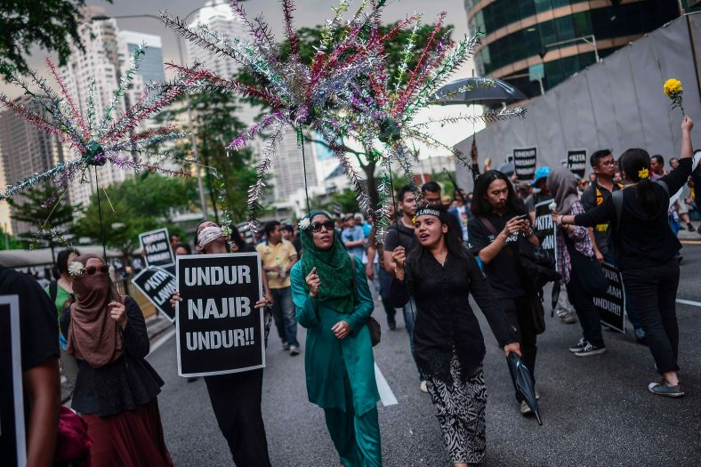 Supporters of Malaysia's opposition leader Anwar Ibrahim hold placards during 'KitaLawan' (We Fight) rally in Kuala Lumpur on March 28, 2015. #KitaLawan rally today will call for opposition leader Datuk Seri Anwar Ibrahim's release from jail where he is serving time for sodomy, and for Prime Minister Datuk Seri Najib Razak's resignation. The demonstration has added opposition to the 6% goods and services tax (GST) to today's agenda and also coincides with the wedding reception of Najib's daughter, Nooryana Najwa, held at the Kuala Lumpur Convention Centre on the same day. photo Adib Rawi Yahya