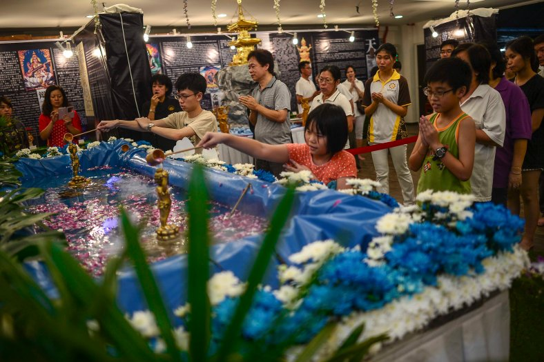 Buddhist devotees sprinkle flowers and pour scented blessed water over an image of an infant Prince, the Prince's image embodies the enlightened presence of the Buddha at Temple in Butterworth on May 02, 2015. Vesak Day is the most important of the Buddhist festivals referred to as 'Buddha's Birthday' with the special day being commemorated in honoring the birth, enlightenment (nirvana) as well as passing away(Parinirvana) of Siddhartha Gautama Buddha. photo Adib Rawi Yahya