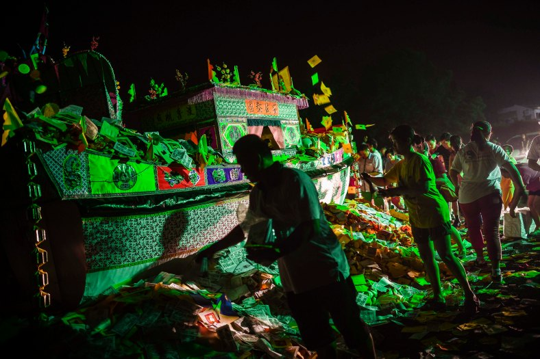 Ethnic Chinese devotees throw 'hell money' before setting fire to a paper-made boat during the festive event of Hungry Ghost festival outside Kuala Lumpur on August 23, 2015. During the month-long festival, Chinese people make offerings of food,
