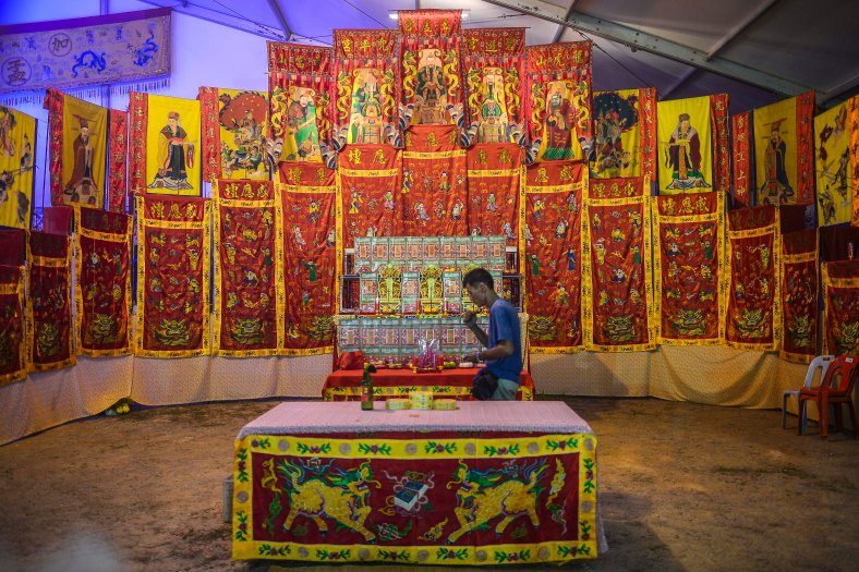 Ethnic Chinese devotees perform prayers during the festive event of Hungry Ghost festival outside Kuala Lumpur on August 23, 2015. During the month-long festival, Chinese people make offerings of food,