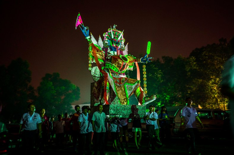 Worshippers carries a paper-made statue of Chinese deity known as