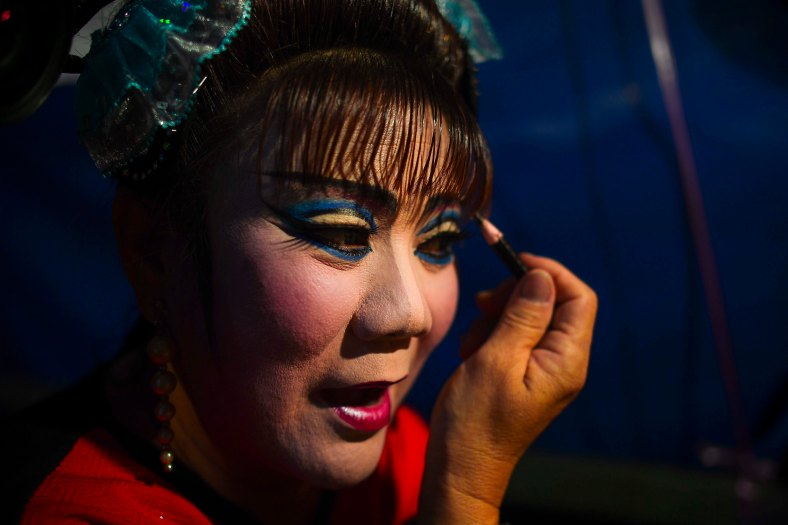 Chinese opera actress puts on makeup at a makeshift theater during the festive event of Hungry Ghost festival outside Kuala Lumpur on August 25, 2015. During the month-long festival, Chinese people make offerings of food,