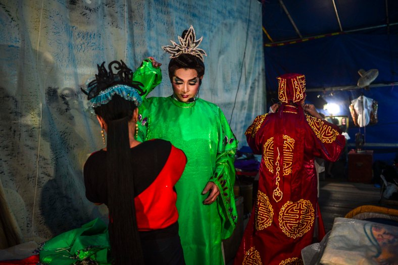 Chinese opera actress prepare themselves before performs at a makeshift theater during the festive event of Hungry Ghost festival outside Kuala Lumpur on August 25, 2015. During the month-long festival, Chinese people make offerings of food,