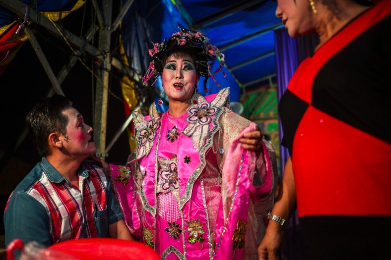 Chinese opera actor joked before their show began at a makeshift theater during the festive event of Hungry Ghost festival outside Kuala Lumpur on August 25, 2015. During the month-long festival, Chinese people make offerings of food,