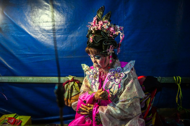 Chinese opera actress wait for her show began at a makeshift theater during the festive event of Hungry Ghost festival outside Kuala Lumpur on August 25, 2015. During the month-long festival, Chinese people make offerings of food,