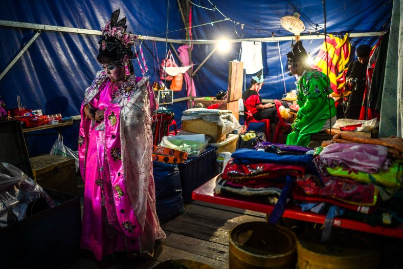 Chinese opera actress wait for their show began at a makeshift theater during the festive event of Hungry Ghost festival outside Kuala Lumpur on August 25, 2015. During the month-long festival, Chinese people make offerings of food,