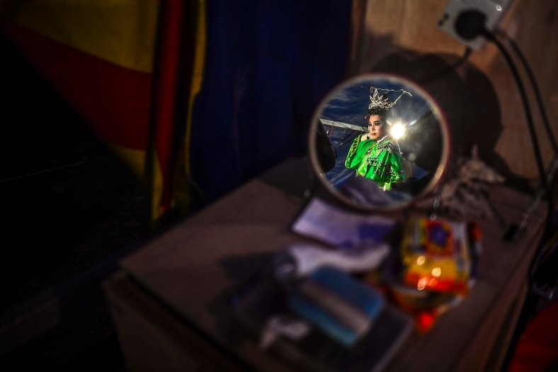 Chinese opera actress wait for his show began at a makeshift theater during the festive event of Hungry Ghost festival outside Kuala Lumpur on August 25, 2015. During the month-long festival, Chinese people make offerings of food,