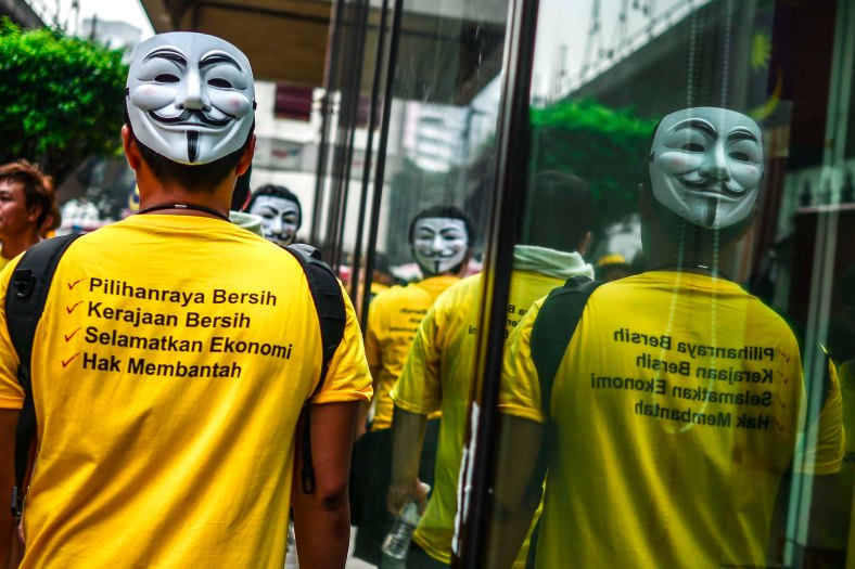 Protesters with a mask are reflected on a mirror during the second day Bersih 4.0 rally at Dataran Merdeka on August 30, 2015. The Bersih 4.0 rally is a series of planned rallies to be carried out on 29 to 30 August in major cities in Malaysia, namely Kuching, Kota Kinabalu and Kuala Lumpur. This rally being carried out with the objective to seeking the resignation of Malaysian Prime Minister Najib Tun Razak and calling for clean governance in Malaysia and follow up to similar rallies that were carried out in 2007, 2011 and 2012. The assembly is being held for 34 hours, starting at 2:00 pm on August 29 until the Merdeka countdown on August 31. However, the rally ended peacefully. photo adib rawi yahya