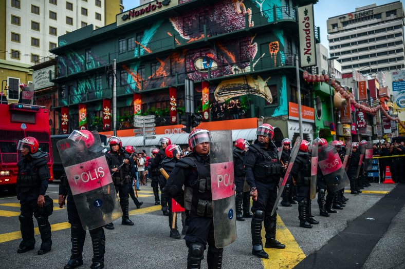 Riot police stand guard near the main entrance of Petaling Street in Kuala Lumpur on September 16, 2015. In what was to be a day to celebrate the anniversary of the 52th formation of Malaysia as a nation, thousands of people in Red Rallied in Kuala Lumpur on September 16 in a show of support for Prime Minister Datuk Seri Najib Razak. The rally organised by Himpunan Rakyat Bersatu and backed by pro government bodies saw thousands dressed in red in the heart of the city. The rally was condemned by some for its racial slurs but leaders from the ruling UMNO have denied this and have openly backed the rally. photo adib rawi yahya