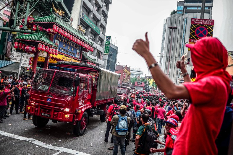 A protester gesture to the riot police while stand guard at the main entrance of Petaling Street in Kuala Lumpur on September 16, 2015. In what was to be a day to celebrate the anniversary of the 52th formation of Malaysia as a nation, thousands of people in Red Rallied in Kuala Lumpur on September 16 in a show of support for Prime Minister Datuk Seri Najib Razak. The rally organised by Himpunan Rakyat Bersatu and backed by pro government bodies saw thousands dressed in red in the heart of the city. The rally was condemned by some for its racial slurs but leaders from the ruling UMNO have denied this and have openly backed the rally. photo adib rawi yahya