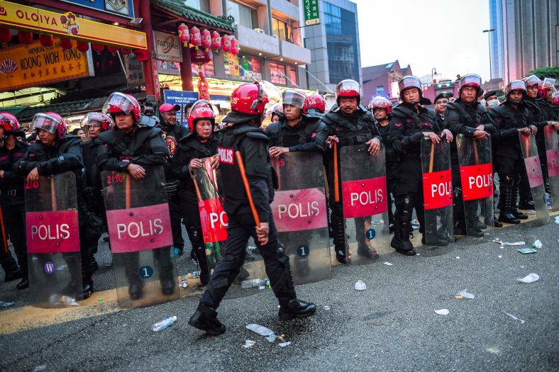 Riot police stand guard at the main entrance of Petaling Street in Kuala Lumpur on September 16, 2015. In what was to be a day to celebrate the anniversary of the 52th formation of Malaysia as a nation, thousands of people in Red Rallied in Kuala Lumpur on September 16 in a show of support for Prime Minister Datuk Seri Najib Razak. The rally organised by Himpunan Rakyat Bersatu and backed by pro government bodies saw thousands dressed in red in the heart of the city. The rally was condemned by some for its racial slurs but leaders from the ruling UMNO have denied this and have openly backed the rally. photo adib rawi yahya