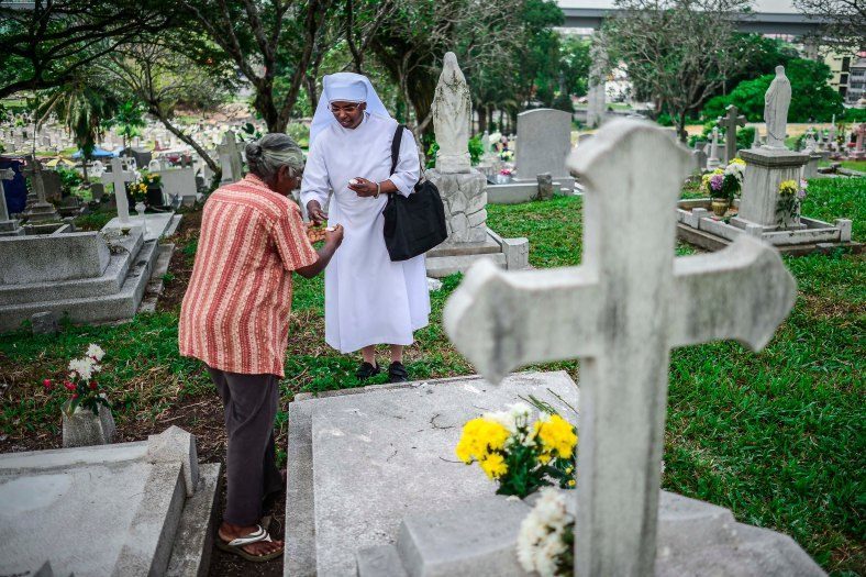 "Relatives light candle and offer prayers at the tomb stone of their departed love ones during All Souls Day festival at a cemetery outside Kuala Lumpur on November 2, 2015. All Souls Day is a day of prayer for the dead, particularly but not exclusively one's relatives which is observed on Nov 2 every year, also goes by its official name as ""The Commemor­ation of All the Faithful Departed"". photo adib rawi yahya"