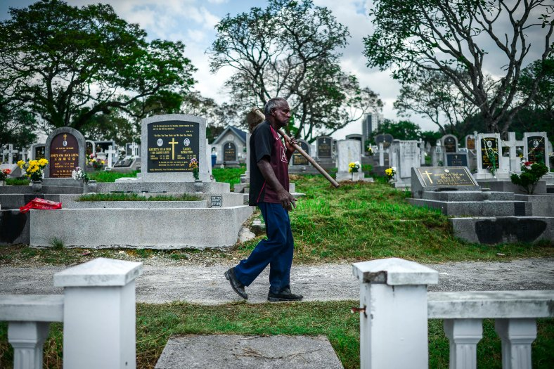"""A man walk past the tomb stone during All Souls Day festival at a cemetery outside Kuala Lumpur on November 2, 2015. All Souls Day is a day of prayer for the dead, particularly but not exclusively one's relatives which is observed on Nov 2 every year, also goes by its official name as """"The Commemoration of All the Faithful Departed"""". photo adib rawi yahya"""