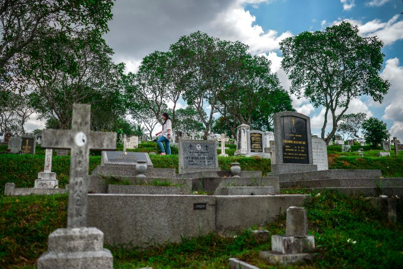 """A woman walk past the tomb stone during All Souls Day festival at a cemetery outside Kuala Lumpur on November 2, 2015. All Souls Day is a day of prayer for the dead, particularly but not exclusively one's relatives which is observed on Nov 2 every year, also goes by its official name as """"The Commemoration of All the Faithful Departed"""". photo adib rawi yahya"""