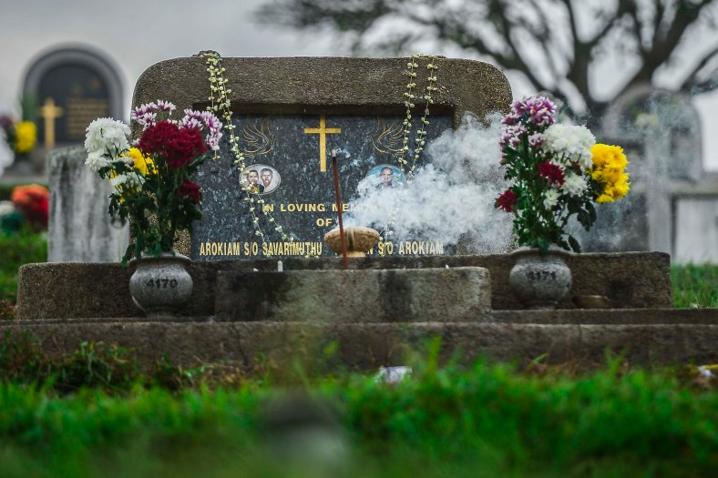 """Relatives puts the flowers and light candle after offer prayers at the tomb stone of their departed love ones during All Souls Day festival at a cemetery outside Kuala Lumpur on November 2, 2015. All Souls Day is a day of prayer for the dead, particularly but not exclusively one's relatives which is observed on Nov 2 every year, also goes by its official name as """"The Commemoration of All the Faithful Departed"""". photo adib rawi yahya"""