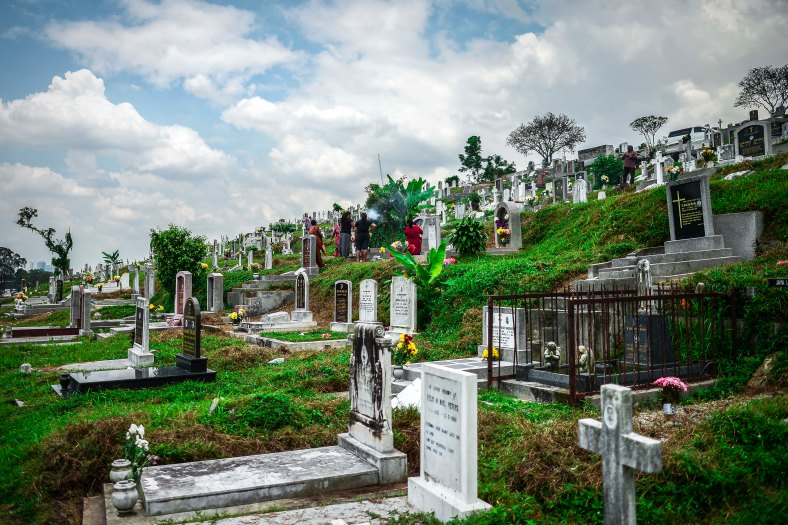 """Family relatives offer prayers at the tomb stone of their departed love ones during All Souls Day festival at a cemetery outside Kuala Lumpur on November 2, 2015. All Souls Day is a day of prayer for the dead, particularly but not exclusively one's relatives which is observed on Nov 2 every year, also goes by its official name as """"The Commemoration of All the Faithful Departed"""". photo adib rawi yahya"""