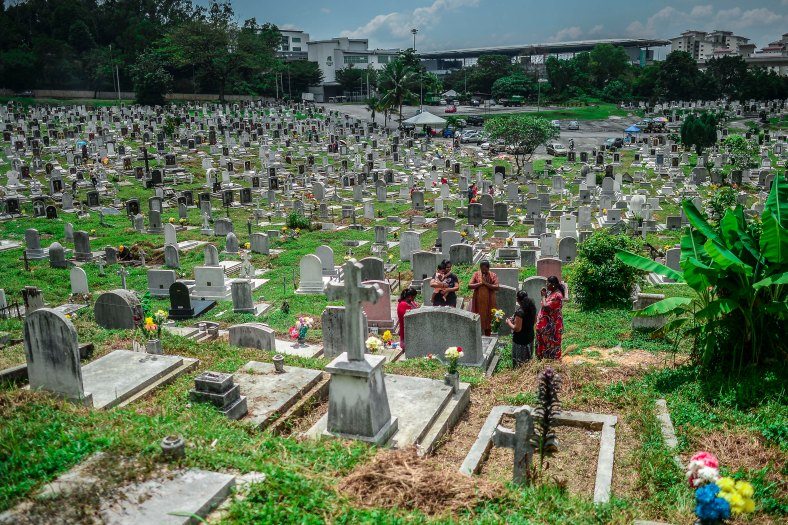 "Family relatives offer prayers at the tomb stone of their departed love ones during All Souls Day festival at a cemetery outside Kuala Lumpur on November 2, 2015. All Souls Day is a day of prayer for the dead, particularly but not exclusively one's relatives which is observed on Nov 2 every year, also goes by its official name as ""The Commemor­ation of All the Faithful Departed"". photo adib rawi yahya"
