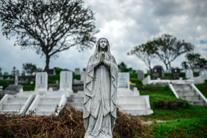"""The tomb stone at a cemetery during All Souls Day festival at a cemetery outside Kuala Lumpur on November 2, 2015. All Souls Day is a day of prayer for the dead, particularly but not exclusively one's relatives which is observed on Nov 2 every year, also goes by its official name as """"The Commemoration of All the Faithful Departed"""". photo adib rawi yahya"""