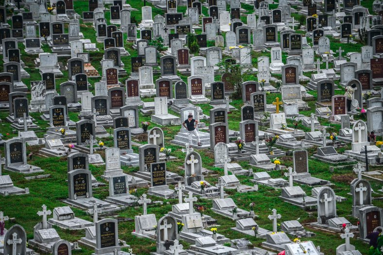"""A man stands near the tomb stone of their departed love ones during All Souls Day festival at a cemetery outside Kuala Lumpur on November 2, 2015. All Souls Day is a day of prayer for the dead, particularly but not exclusively one's relatives which is observed on Nov 2 every year, also goes by its official name as """"The Commemoration of All the Faithful Departed"""". photo adib rawi yahya"""