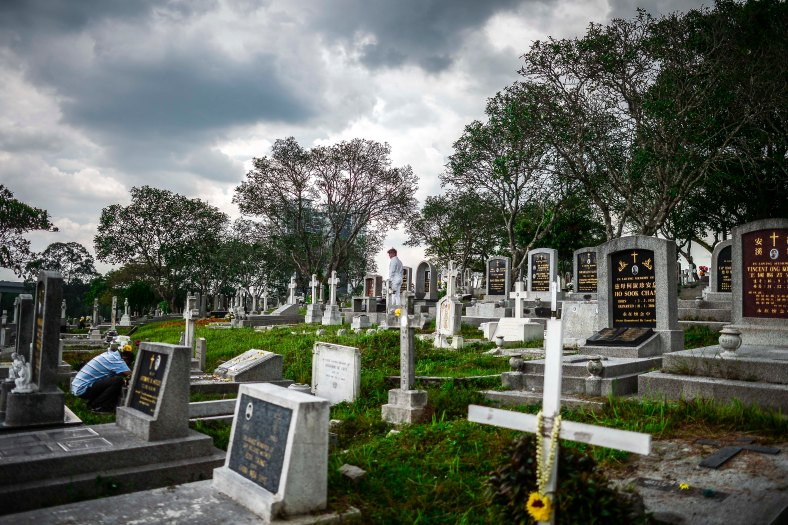 "Relatives offer prayers at the tomb stone of their departed love ones during All Souls Day festival at a cemetery outside Kuala Lumpur on November 2, 2015. All Souls Day is a day of prayer for the dead, particularly but not exclusively one's relatives which is observed on Nov 2 every year, also goes by its official name as ""The Commemor­ation of All the Faithful Departed"". photo adib rawi yahya"